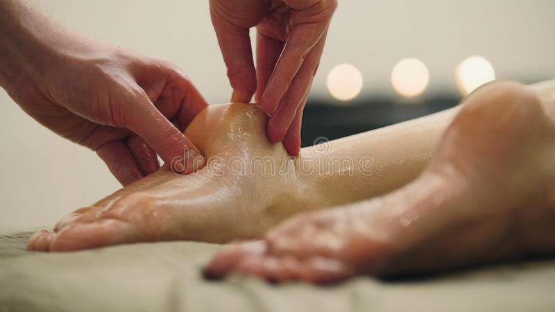 Sesame oil massage for heel foot. Relaxation treatment for young woman, close up stock image
