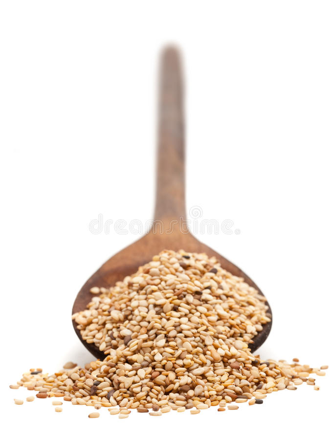 Sesame seeds. On wooden spoon over white background stock photos