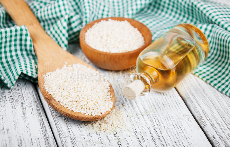 Sesame seeds and bottle with oil. On a old wooden table stock photos