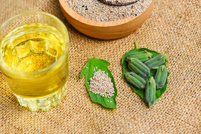 Sesame seeds in a wooden bowl and green leaf with sesame oil glass stock photo