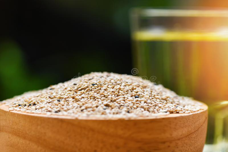 Sesame seeds in wooden bowl with Sesame oil in glass stock images