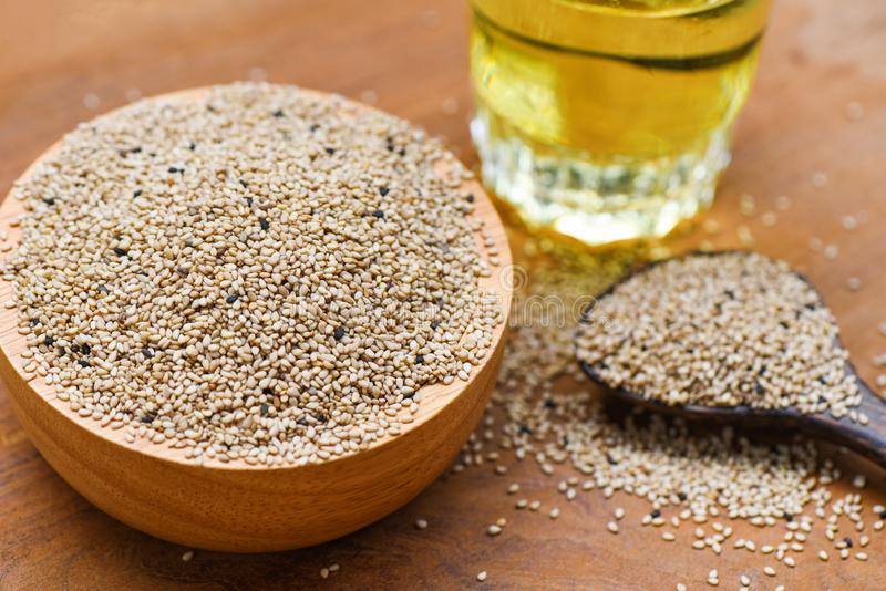 Sesame seeds in wooden bowl and spoon with Sesame oil in glass royalty free stock photography