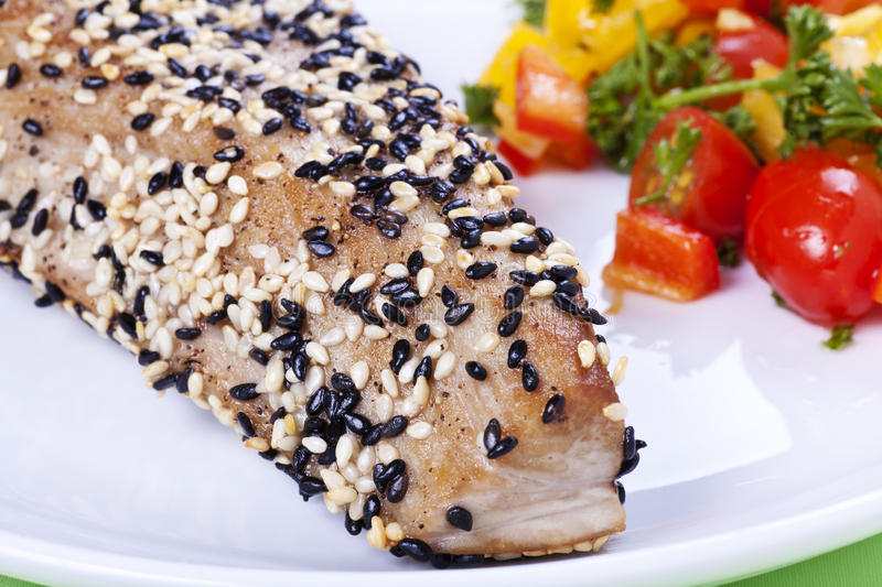 Sesame tuna steak. Yellow-fin tuna steak with sesame seeds and vegetables - detail royalty free stock images