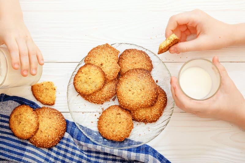 Sesamkoekjes met melk voor ontbijt voor kinderen De kinderen ` s dient het kader in De kinderen eten koekjes stock foto