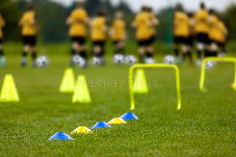 Sesión de formación del fútbol Balones de fútbol, pilones, conos, marcas y obstáculos del entrenamiento en echada de la hierba foto de archivo