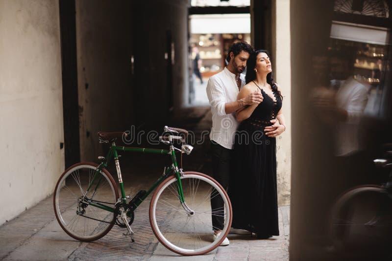 Sesión de foto de los pares del amor Un hombre y una mujer están caminando en la ciudad vieja con una bici retra verde fotografía de archivo libre de regalías