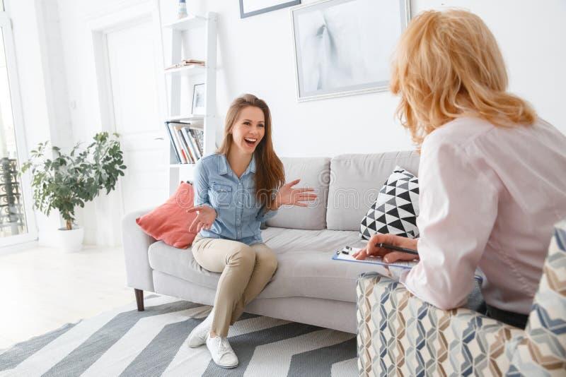 Sesión de terapia femenina del psychologyst con el cliente dentro que sienta a la muchacha que habla de vida imagen de archivo libre de regalías