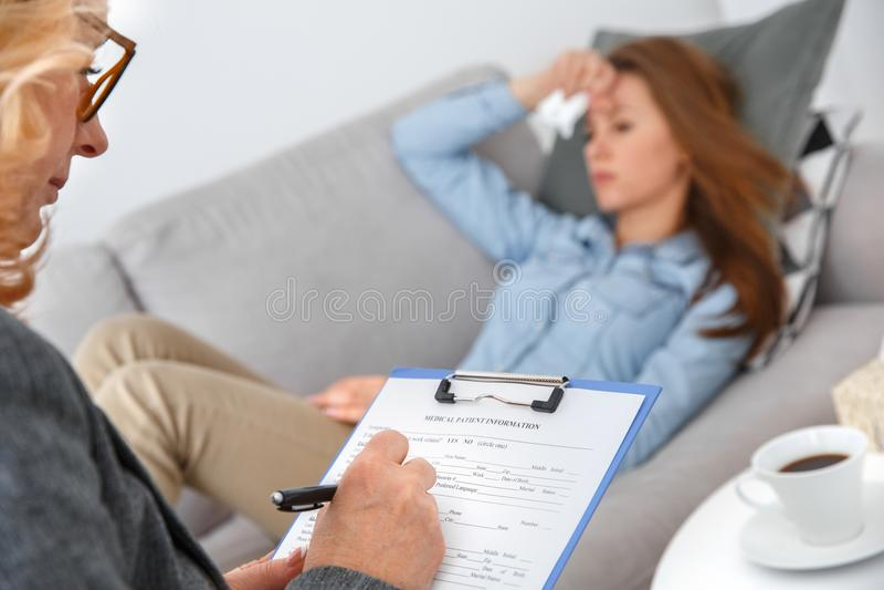 Sesión de terapia femenina del psychologyst con el cliente que miente en el sofá dentro que satisface la forma imágenes de archivo libres de regalías