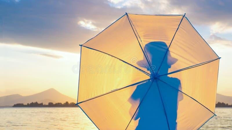 Sesja zdjęciowa. tło Elegancki modniś, chłopiec w kapeluszu z parasolem na seashore Sylwetka mężczyzna z powrotem przegląda dalej fotografia royalty free