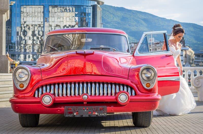 sessão fotográfica editorial da noiva em um carro velho do temporizador do vintage vermelho bonito dos anos sessenta em um centro imagens de stock royalty free