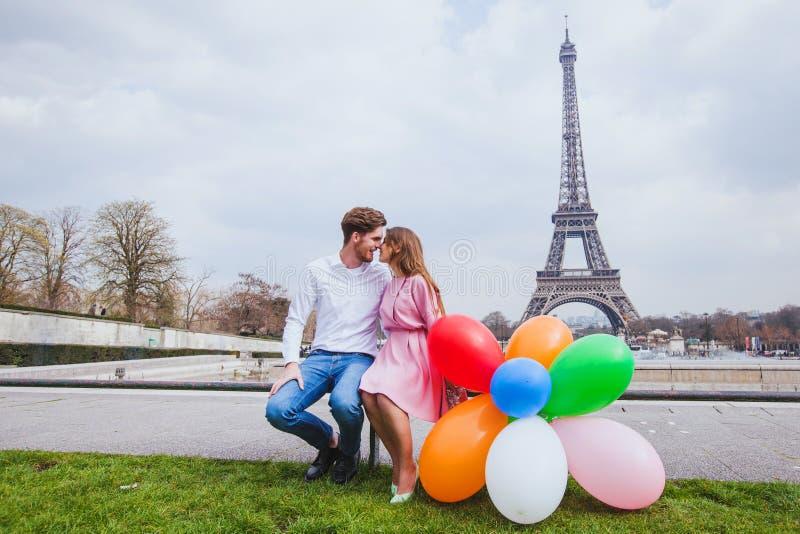 Sessão fotográfica, par feliz com os balões que levantam perto da torre Eiffel em Paris imagens de stock royalty free