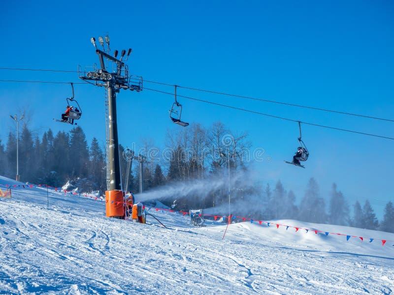 Sessellift, Skifahrer und Schneekanonen in Aktion lizenzfreie stockbilder