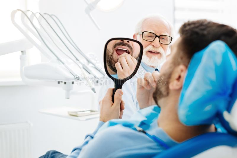Close up of the patient at the dentists. Session completed. Close up of young men holding dental mirror and looking at his teeth after being cured by stock photography