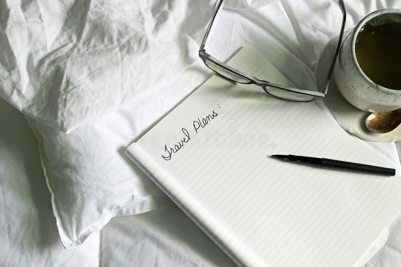 Session confortable de planification de plans de voyage dans le lit avec le thé images stock
