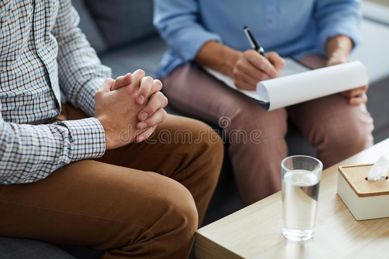 Session of counselor. Tense patient of counselor keeping his hand in hand while sitting next to psychologist during conversation stock photo