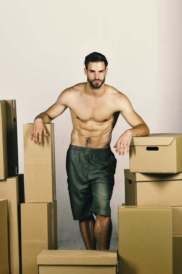 Sessualità e muoversi nel concetto: uomo sexy fra le scatole fotografia stock