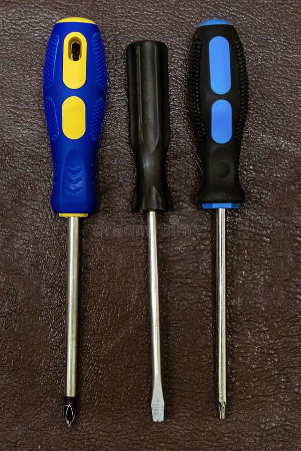 Set śrubokrętów trzy naprawiania ręcznych narzędzi domowy repairman na ciemnej tło projekta bazie fotografia stock