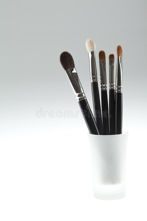 A set of 5 make-up brushes set in a small glass royalty free stock images