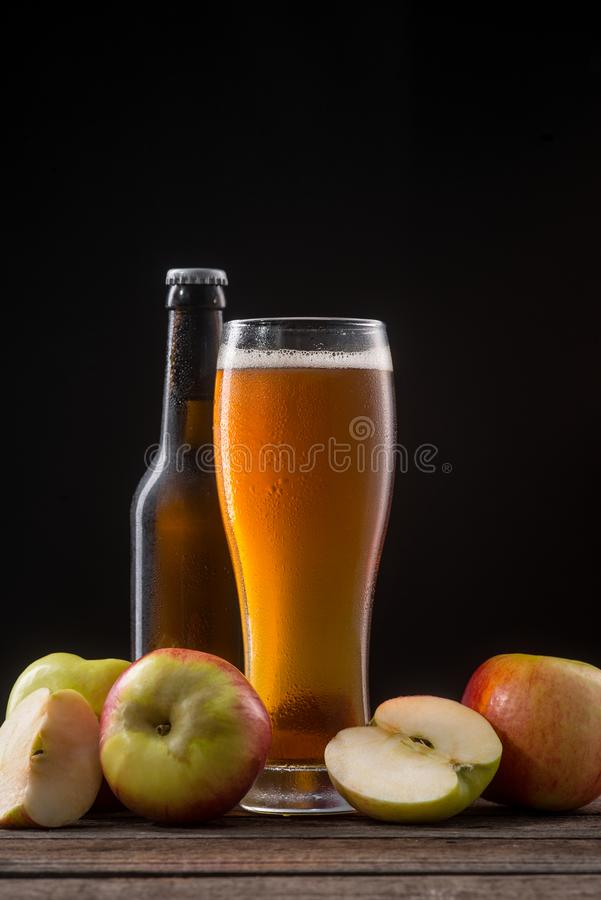 Set of apples and cider. Bottle and tall glass of alcoholic drink with whole and sliced fruits on a rustic table. Still life on black, vertical orientation stock photography