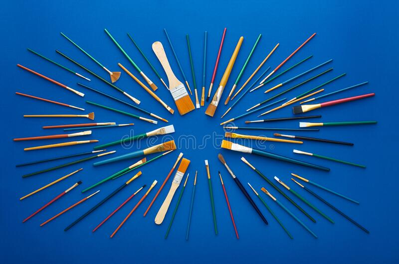 Set of paint brushes in circular burst pattern. Flat lay shot, blue background. Set of art paint brushes of various color, size and bristle type laid out in stock photo