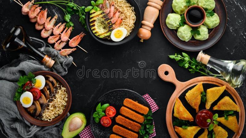 Set Asian food. Noodles, shrimp, Samsa, khinkali. On a black wooden background. royalty free stock photography