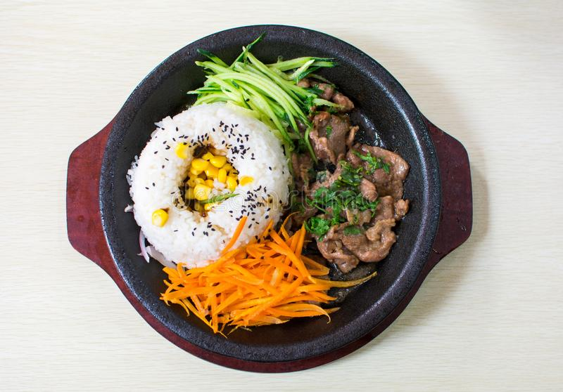 A set of meal with rice, beef, cucumber and carrot served on the. A set of asian meal with rice, beef, cucumber and carrot served on the dark plate stock photography