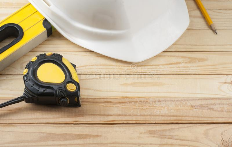 Construction tools and white helmet on wooden background .Copy space for text. stock photography