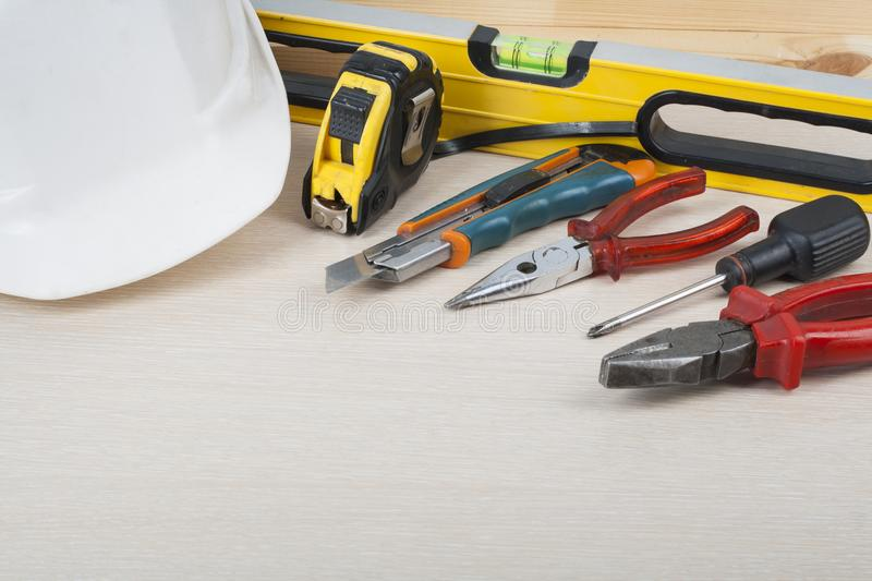 Construction tools and white helmet on wooden background. Copy space for text. royalty free stock image