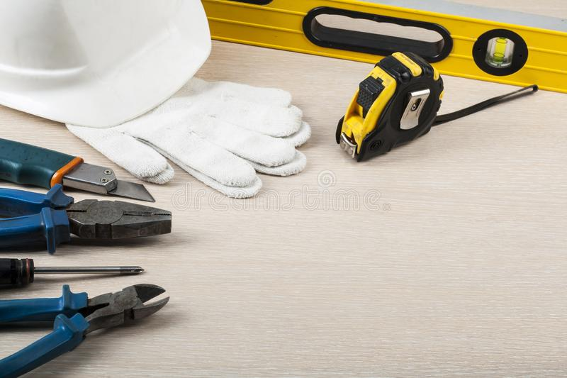 Construction tools and white helmet on wooden background. Copy space for text stock photography