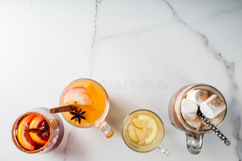 Set of 4 autumn drinks. Selection of various autumn traditional drinks: hot chocolate with marshmallow, tea with lemon and ginger, white pumpkin spicy sangria royalty free stock photos
