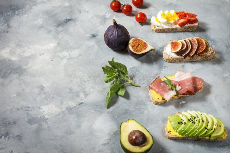 Set avocado kanapki, czereśniowi pomidory i jajka, figi, prochutto na betonowym tle obraz stock