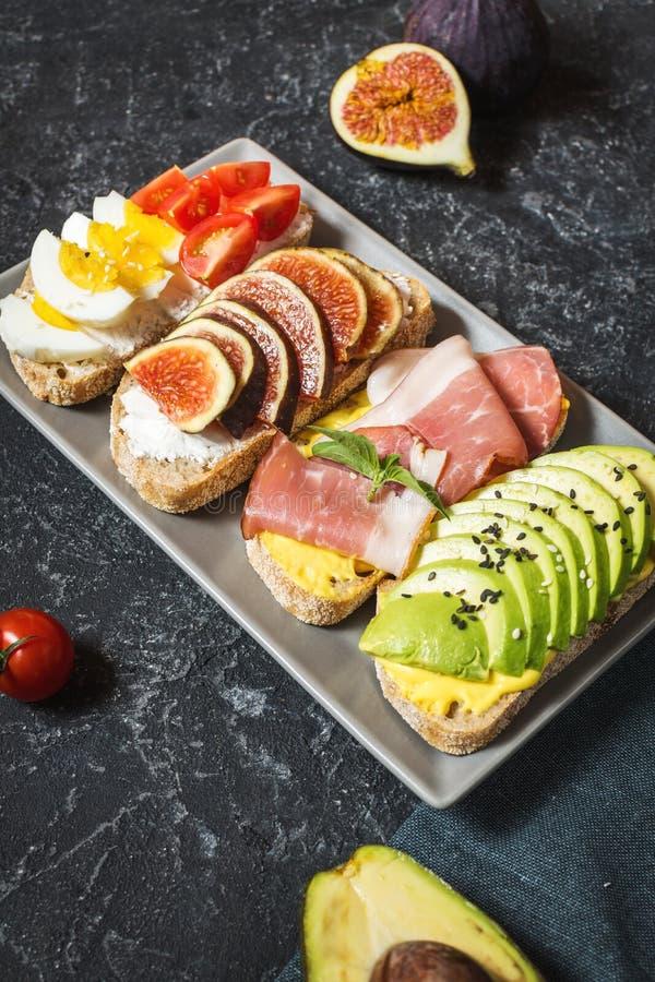 Set avocado kanapki, czereśniowi pomidory i jajka, figi, prochutto na kamiennym tle zdjęcia royalty free