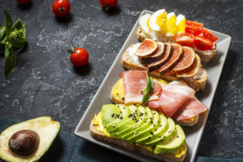 Set avocado kanapki, czereśniowi pomidory i jajka, figi, prochutto na kamiennym tle zdjęcie royalty free