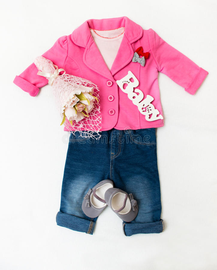 Set of baby girl clothes on holiday. Jacket, leggings, bodykit, booties, a bouquet of flowers stock photo