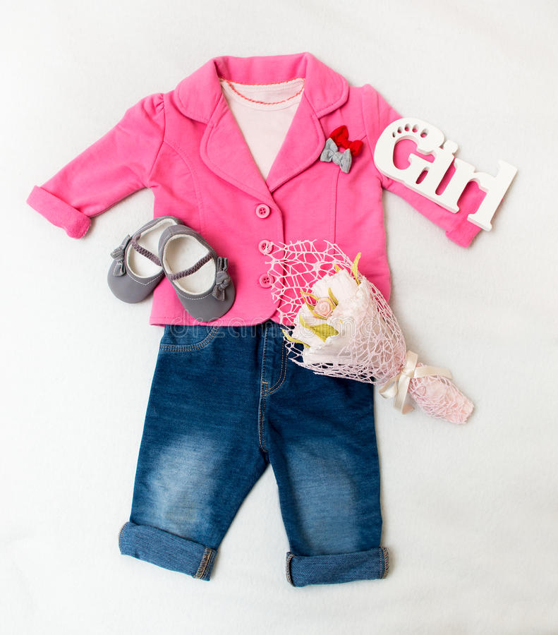 Set of baby girl clothes on holiday. Jacket, leggings, bodykit, booties, a bouquet of flowers royalty free stock image