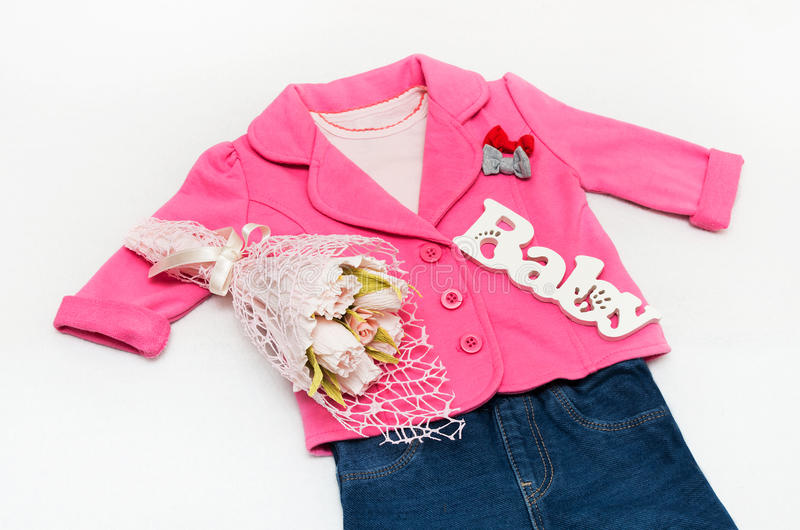 Set of baby girl clothes on holiday. Jacket, leggings, bodykit, booties, a bouquet of flowers royalty free stock images