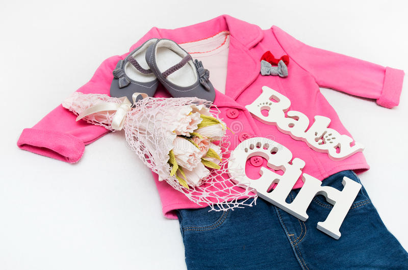 Set of baby girl clothes on holiday. Jacket, leggings, bodykit, booties, a bouquet of flowers stock photography