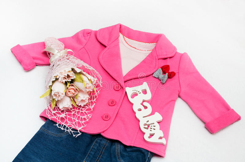 Set of baby girl clothes on holiday. Jacket, leggings, bodykit, booties, a bouquet of flowers stock images