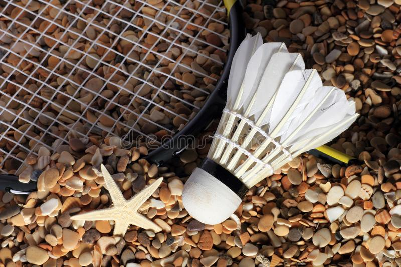 Set Badminton racket and shuttlecock feathers on rocks, beach background. royalty free stock photo
