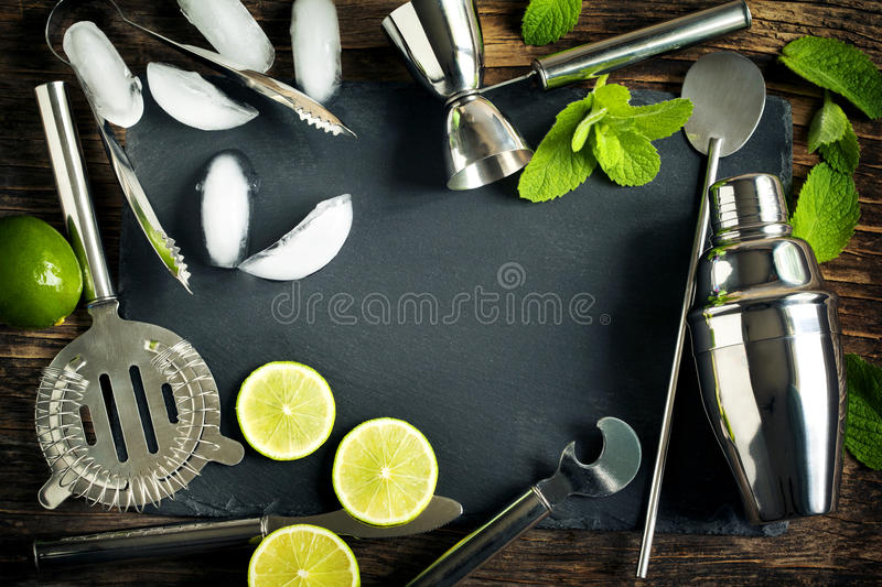 Set of bar accessories and ingredients for making a cocktails arranged. On a wooden background with black board for copy space royalty free stock photography