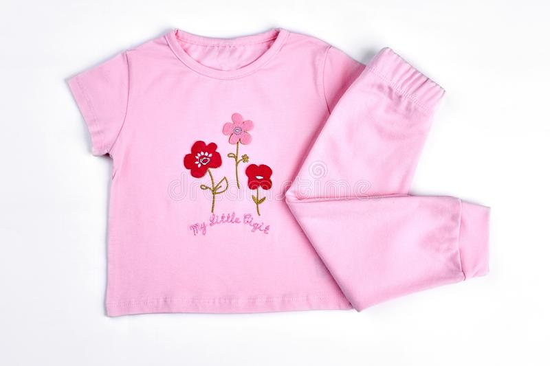 Set of beautiful clothes for baby-girl. Pink cartoon t-shirt and leggings for infant girls, white background royalty free stock images