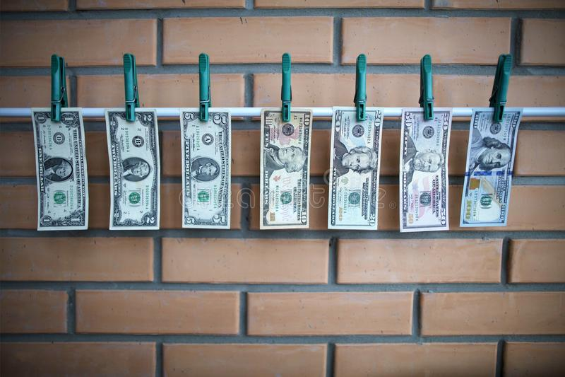 Concept of money laundering - dollars are drying on lath on on brick wall background. Set of bills 1,2,5,10,20,50,100 dollars usa are drying on a white lath with stock images
