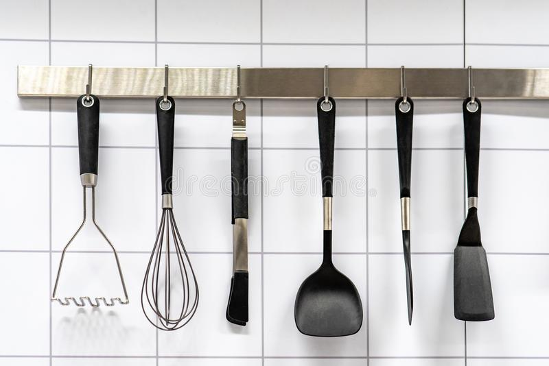 Set of cooking utensils hanging on kitchen wall royalty free stock images