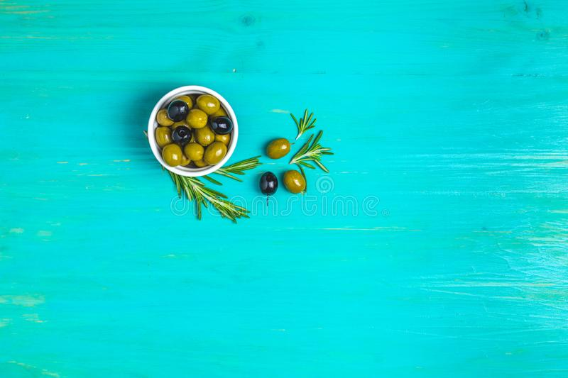 Set of black and green olives on plates, olive oil and rosemary. On a blue turquoise wooden table background. Top view, copy space royalty free stock photos