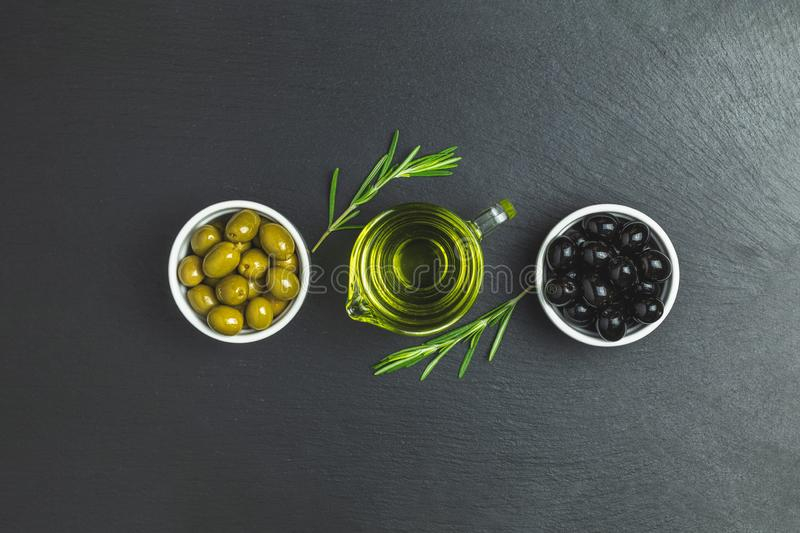 Set of black and green olives on plates, olive oil and rosemary. On a black stone background. Top view, copy space stock image