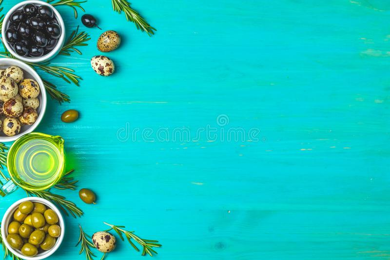 Set of black and green olives, quail eggs on plates, olive oil a. Nd rosemary, on a blue turquoise wooden table background. Top view, copy space stock photos