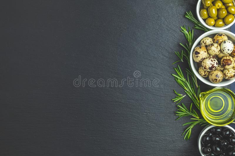 Set of black and green olives, quail eggs on plates, olive oil a. Nd rosemary, on a black stone background. Top view, copy space royalty free stock image