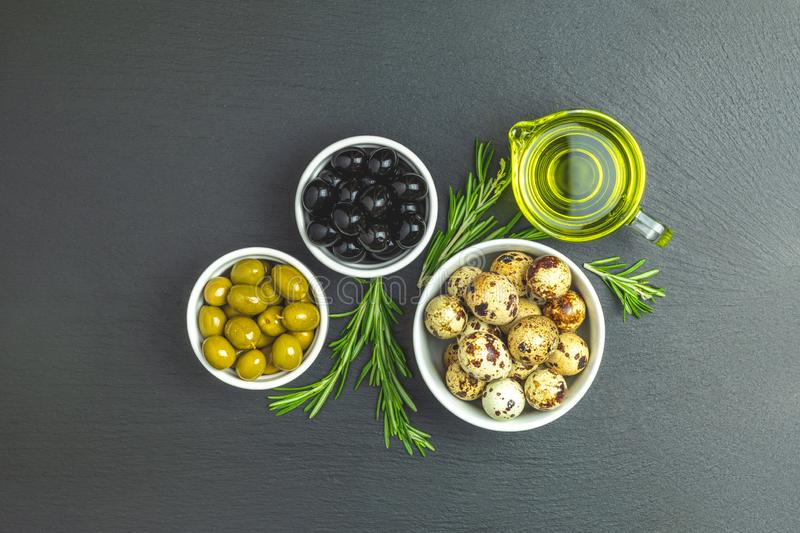 Set of black and green olives, quail eggs on plates, olive oil a. Nd rosemary, on a black stone background. Top view, copy space royalty free stock images