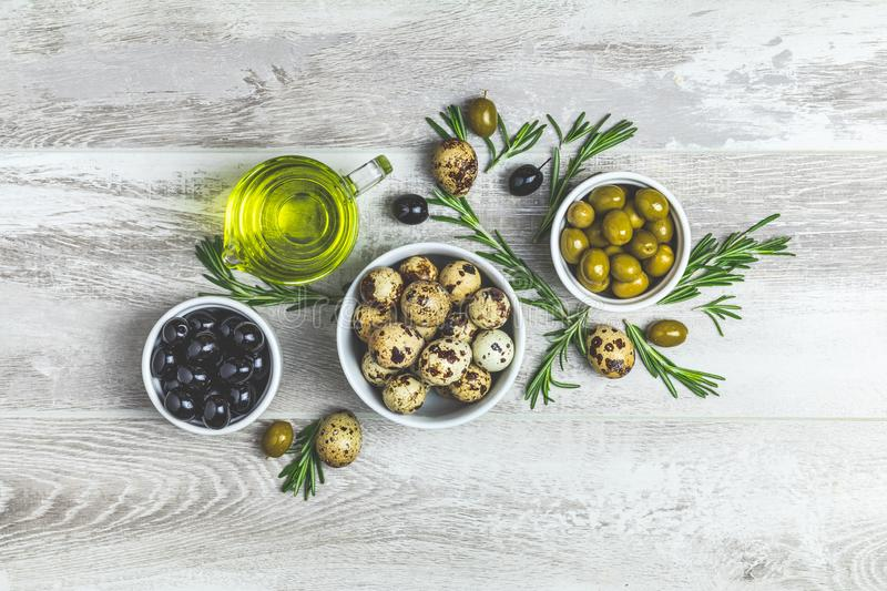 Set of black and green olives, quail eggs on plates, olive oil a. Nd rosemary, on a light gray wooden background. Top view, copy space royalty free stock photos