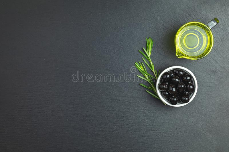 Set of black olives on plate, olive oil and rosemary. On a black stone background. Free space for text stock photos